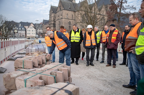 Rudolf Lotz vom städtischen Fachdienst Tiefbau begutachtet bei einem Besichtigungstermin der Baustelle die Konsolensteine, die nach der Restaurierung wieder in die Weidenhäuser Brücke eingebaut werden.©Patricia Grähling, Stadt Marburg