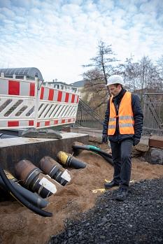 Eine Vielzahl an Leitungen und Rohren werden entlang der Weidenhäuser Brücke über die Lahn geführt. Thomas Engelbach, Fachdienstleiter Tiefbau, zeigt, wo die Rohre in den neuen Fußgängersteg geführt werden.©Patricia Grähling, Stadt Marburg