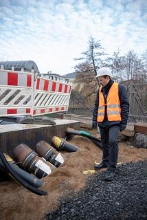 Eine Vielzahl an Leitungen und Rohren werden entlang der Weidenhäuser Brücke über die Lahn geführt. Thomas Engelbach, Fachdienstleiter Tiefbau, zeigt, wo die Rohre in den neuen Fußgängersteg geführt werden.