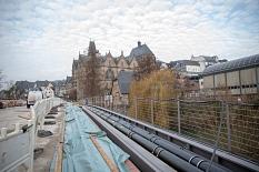 Geordnet werden Rohre und Leitungen in einem Steg entlang der Brücke über die Lahn geführt. Eine Abdeckung wird den Steg später verschließen und für Fußgänger*innen begehbar machen.©Patricia Grähling, Stadt Marburg