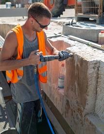 Steinmetze entfernen alte Betonreste an den Sandsteinen.