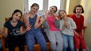 Wellness-Kurs Mädchen - 5 Mädchen sitzen mit Gesichtsmasken auf einer Bank