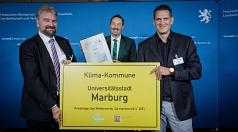 Bürgermeister Wieland Stötzel (links) und Klimaschutzmanager Achim Siehl nehmen den Preis für die Förderung von Balkon-Modulen zur Erzeugung von Strom von Staatssekretär Oliver Conz entgegen.
