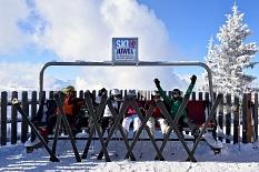 6 Skifahrer sitzen im Schnee auf einer Holliwoodschaukel und ruhen sich aus. An den Füßen haben alle noch ihre Ski, die vor ihnen im Schnee stecken.©Universitätsstadt Marburg