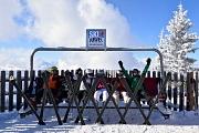 6 Skifahrer sitzen im Schnee auf einer Holliwoodschaukel und ruhen sich aus. An den Füßen haben alle noch ihre Ski, die vor ihnen im Schnee stecken.
