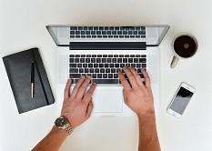 Aus der Vogelperspektive fotografiert zwei Hände, die einen weißen Laptop bedienen, daneben ein Smartphone, eine Tasse Kaffee und ein Notizbuch©stokpic / Pixabay