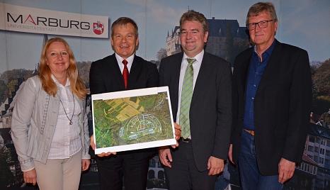 Dr. Griet Newiger-Addy (v. l.), Oberbürgermeister Dr. Thomas Spies, Bürgermeister Wieland Stötzel und Reinhold Kulle präsentieren den Vorschlag zum Wohnungsneubau im Marburger Westen.©Stadt Marburg, Birgit Heimrich